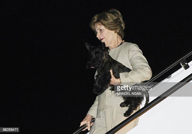 First Lady Laura Bush carries her dog as she steps off Air Force One as they arrive in Waco TX 22 November 2005 US President George W Bush and the...