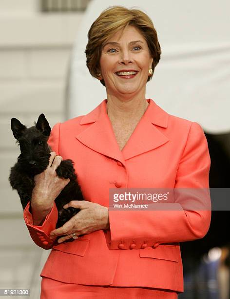 S first lady Laura Bush carries Miss Beazley the Scottish Terrier pup given to her as a birthday present by US President George W Bush during an...