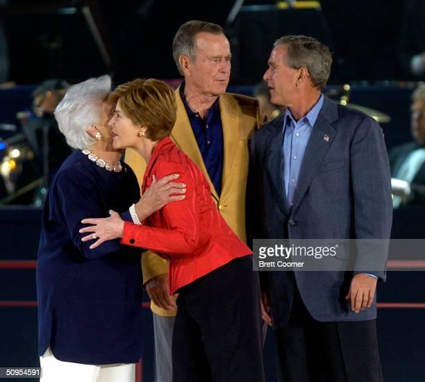 First Lady Laura Bush embraces her motherinlaw Barbara Bush as former President George HW Bush and President George W Bush talk as they are...