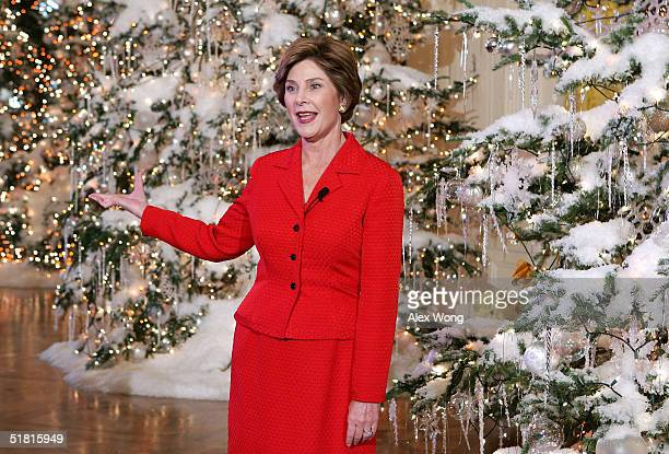 First lady Laura Bush gestures as she reveals the White House Christmas decorations during a press preview at the White House December 2, 2004 in...