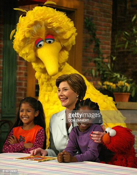 First Lady Laura Bush laughs with Big Bird and Elmo 19 September 2002 while taping a show of Sesame Street in New York The children Sydney Martines...