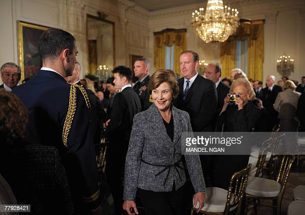 First Lady Laura Bush makes her way from the East Room with US President George W. Bush following the presentation ceremony of the 2007 National...