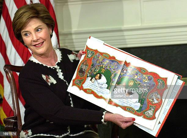 First Lady Laura Bush reads from 'Twas the Night Before Christmas as President George W Bush and about sixty schoolchildren listen December 17 2002...