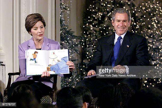 First Lady Laura Bush reads Take a Mouse to the Movies to school children in the East Room of the White House as President George W Bush listens in...