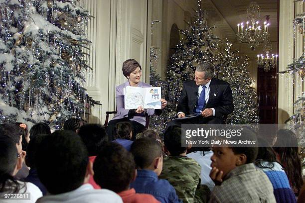 First Lady Laura Bush reads 'Take a Mouse to the Movies' to school children in the East Room of the White House as President George W Bush listens in...