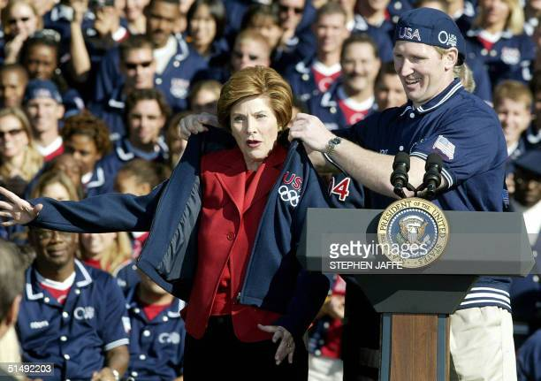 First Lady Laura Bush receives an Olympic jacket from Paraolympic judo athlete Kevin Szott during a ceremony on the South Lawn of the White House...