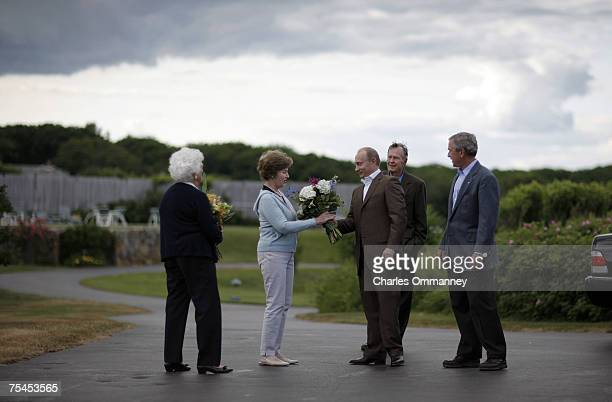 First Lady Laura Bush receives flowers from Russian President Vladamir Putin as he arrives to meet with US President George W Bush at Walker's on...