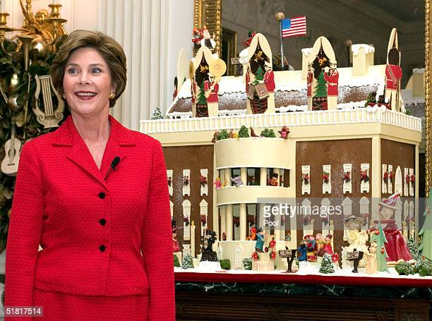 First lady Laura Bush reveals the details of a gingerbread house in the State Dining Room during a press preview tour of the Christmas decorations at...