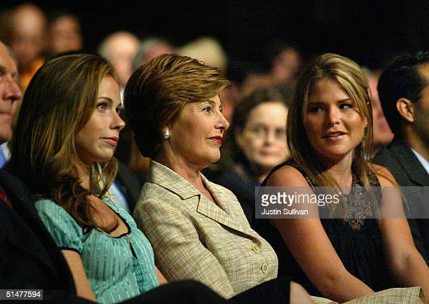 First lady Laura Bush sits with her daughters Barbara and Jenna before the start of the presidential debate between President Bush and Democratic...