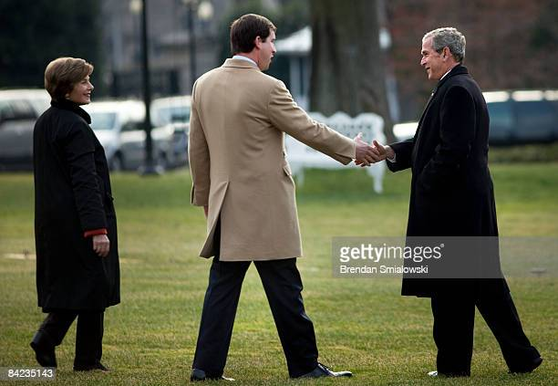 First Lady Laura Bush watches as US President George W Bush greets his soninlaw Henry Hager married to Jenna while walking to Marine One on the South...