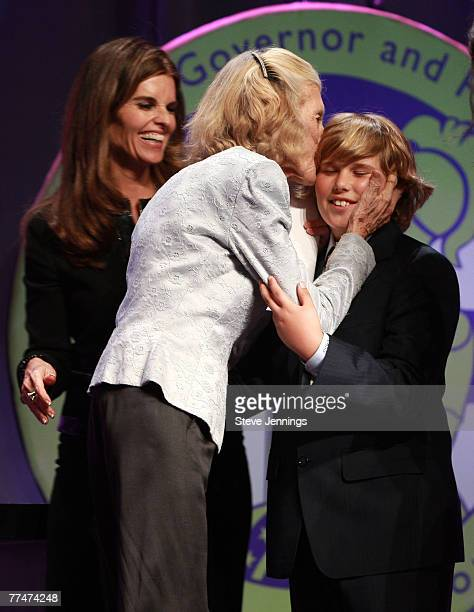 First Lady Maria Shriver looks on as her mother Eunice Kennedy Shriver kisses Christopher Schwarzenegger after being presented the Minerva Lifetime...
