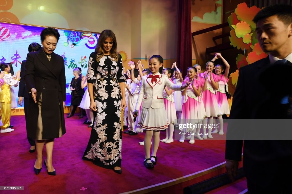 US First Lady Melania Trump (C) and China's First Lady Peng Liyuan (L) are escorted by a student after a cultural performance during a visit to Banchang Primary School in Beijing on November 9, 2017. Donald Trump and Xi Jinping put their professed friendship to the test on November 9 as the least popular US president in decades and the newly empowered Chinese leader met for tough talks on trade and North Korea. /