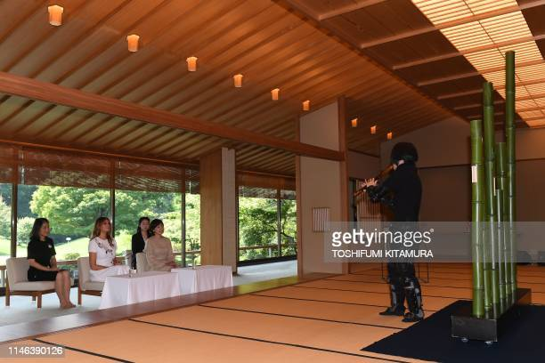 US First Lady Melania Trump and Japan's Premier Shinzo Abe's wife Akie watch an artist play a traditional shakuhachi bambooflute in a Japanese style...