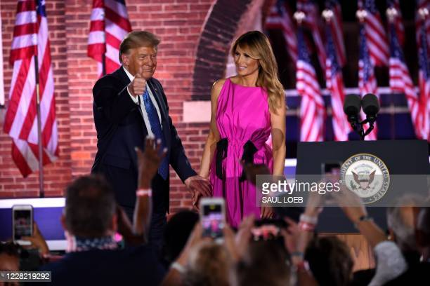 First Lady Melania Trump and US President Donald Trump gestures to attendees during the third night of the Republican National Convention at Fort...