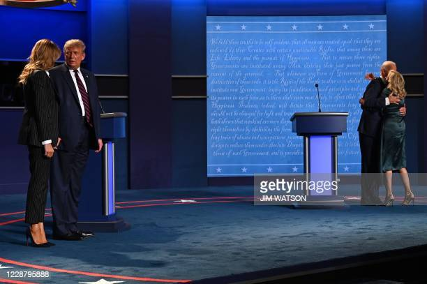 First Lady Melania Trump and US President Donald Trump look at each other, as Democratic Presidential candidate and former US Vice President Joe...