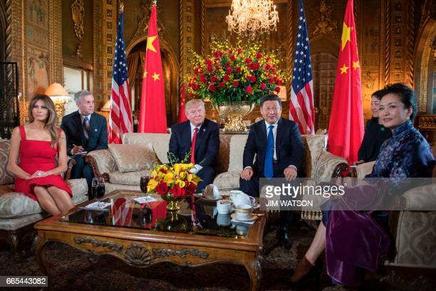 US First Lady Melania Trump and US President Donald Trump pose with Chinese President Xi Jinping and his wife Peng Liyuan upon their arrival to the...