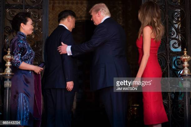 US First Lady Melania Trump and US President Donald Trump welcome Chinese President Xi Jinping and his wife Peng Liyuan to the MaraLago estate in...