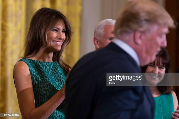First lady Melania Trump claps as United States President Donald J Trump speaks during the Shamrock Bowl Presentation at the White House on March 15...