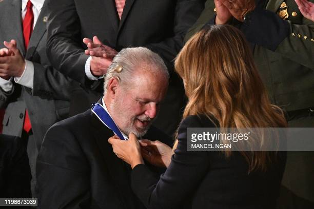 First Lady Melania Trump delivers the Medal of Freedom to radio personality Rush Limbaugh after being acknowledged by US President Donald Trump as he...