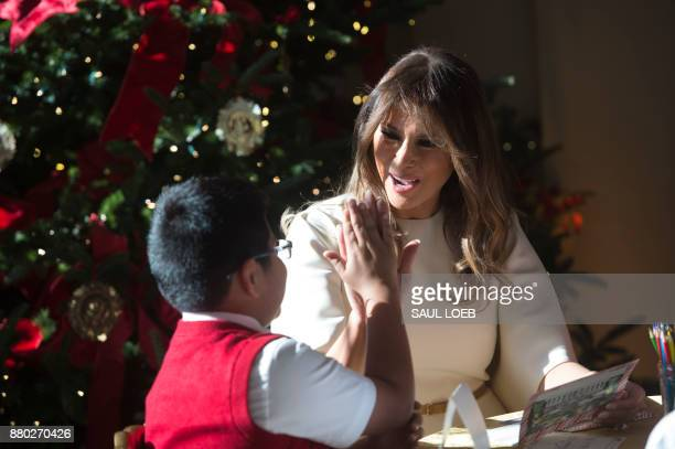 US First Lady Melania Trump gives a boy a highfive as they make holiday cards in the East Wing as she tours Christmas decorations at the White House...