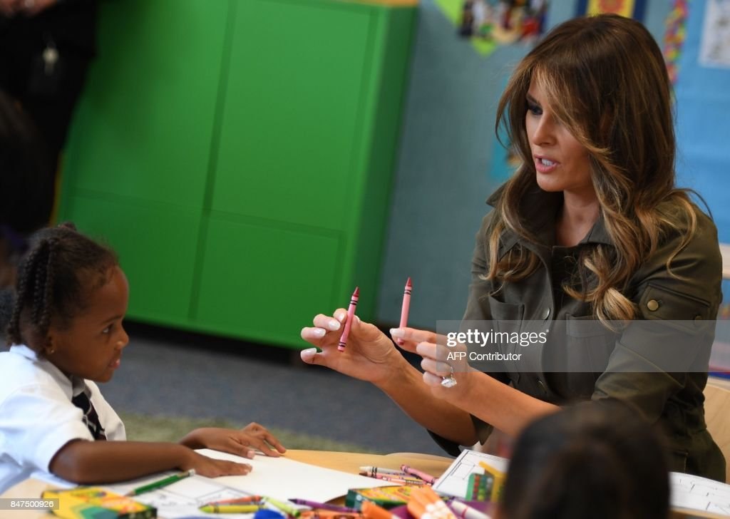 First Lady Melania Trump hands crayons to a student she visits a youth centre at Joint Andrews Airforce base, Maryland on September 15, 2017. /