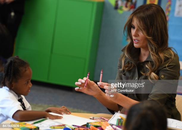 First Lady Melania Trump hands crayons to a student she visits a youth centre at Joint Andrews Airforce base, Maryland on September 15, 2017. / AFP...