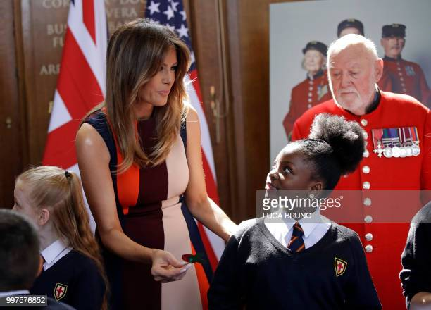 US First Lady Melania Trump helps children to make poppies as she meets British military veterans known as 'Chelsea Pensioners' during a visit to the...
