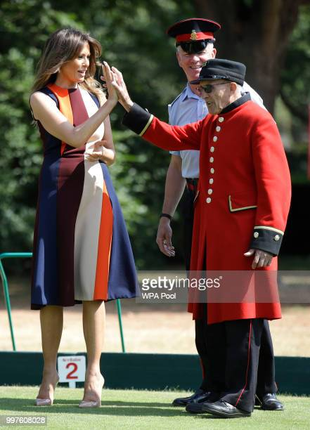 """First Lady Melania Trump high-fives with a British military veteran known as a """"Chelsea Pensioner"""" during a game of bowls at Royal Hospital Chelsea..."""