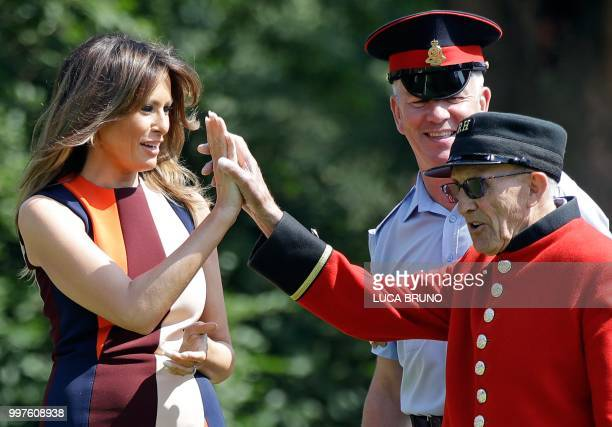 First Lady Melania Trump highfives with a British military veteran known as a Chelsea Pensioner during a game of bowls during a visit to the Royal...