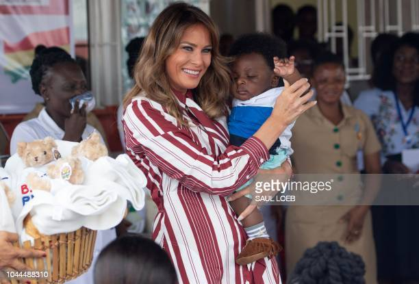 US First Lady Melania Trump holds a baby during a visit to the Greater Accra Regional Hospital in Accra on October 2 as she begins her week long trip...
