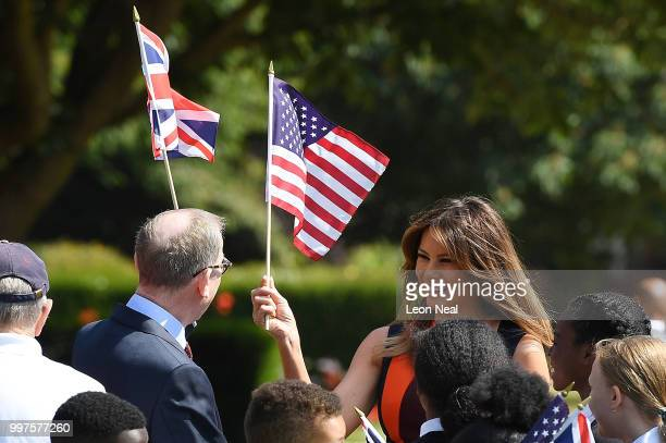 First Lady Melania Trump holds a US flag as she meets British Army veterans known as Chelsea Pensioners at Royal Hospital Chelsea on July 13 2018 in...