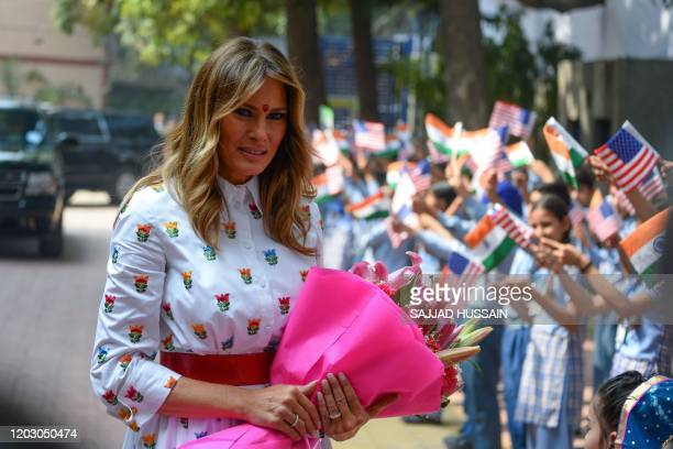 US First Lady Melania Trump holds flowers as she arrives at Sarvodaya CoEd Senior Secondary School in New Delhi on February 25 2020 US President...