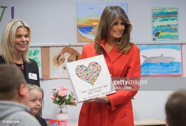US First Lady Melania Trump holds up a gift as she exchanges valentines for Valentine's Day as she visits with children who are currently patients at...