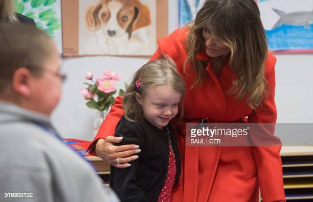 US First Lady Melania Trump hugs a girl as she exchanges valentines for Valentine's Day as she visits with children who are currently patients at the...