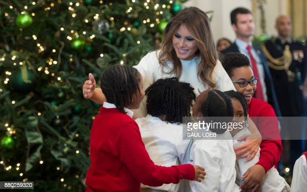 US First Lady Melania Trump hugs children in the East Room as she tours Christmas decorations at the White House in Washington DC November 27 2017 /...