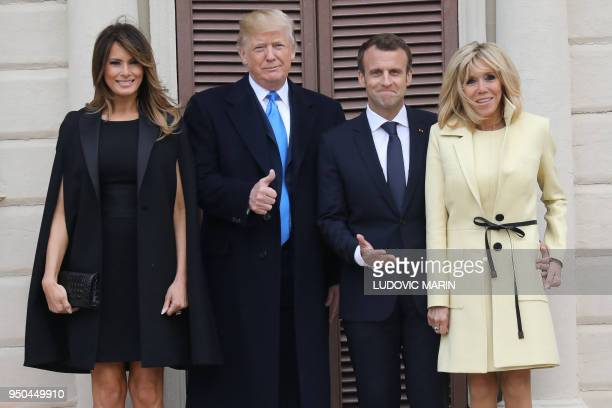 TOPSHOT US first lady Melania Trump husband US President Donald Trump French President Emmanuel Macron and his wife first lady Brigitte Macron pose...