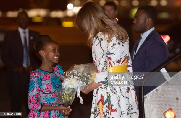US First Lady Melania Trump is greeted by a girl as she disembarks from her military airplane upon arrival at Jomo Kenyatta International Airport in...