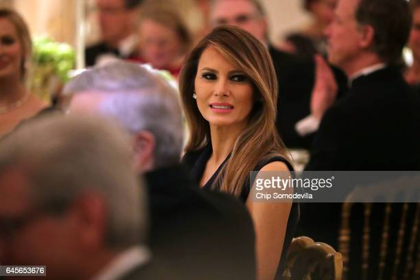 US first lady Melania Trump listens to a toast by her husband President Donald Trump while hosting the annual Governors' Dinner in the East Room of...
