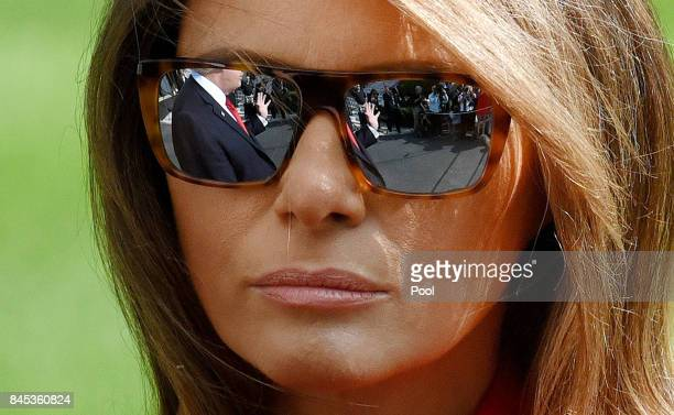 First lady Melania Trump looks as US President Donald Trump is reflected in her glasses and talks to members of the media about hurricane Irma upon...