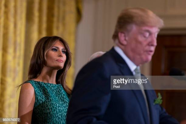 First lady Melania Trump looks on as United States President Donald J Trump speaks during the Shamrock Bowl Presentation at the White House on March...
