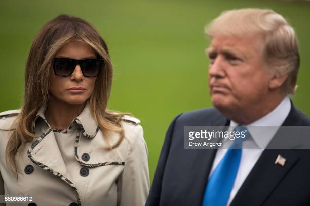 First Lady Melania Trump looks on as U.S. President Donald Trump takes questions from reporters, on their way to Marine One on the South Lawn of the...