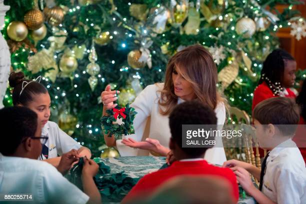 US First Lady Melania Trump makes Christmas decorations with children in the State Dining Room as she tours holiday decorations at the White House in...