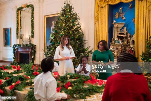 US First Lady Melania Trump makes Christmas garland with children in the East Wing as she tours holiday decorations at the White House in Washington...