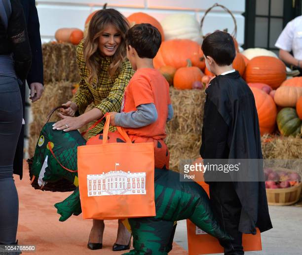 First Lady Melania Trump pets a toy dinosaur as she and President Donald Trump welcome trickortreaters to the White House for Halloween festivities...