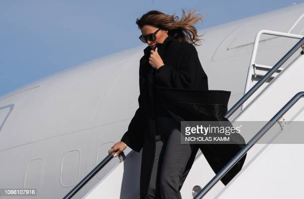 US First Lady Melania Trump protects herself from the wind as she arrives at Andrews Air Force Base in Maryland on November 28 2018 after attending a...