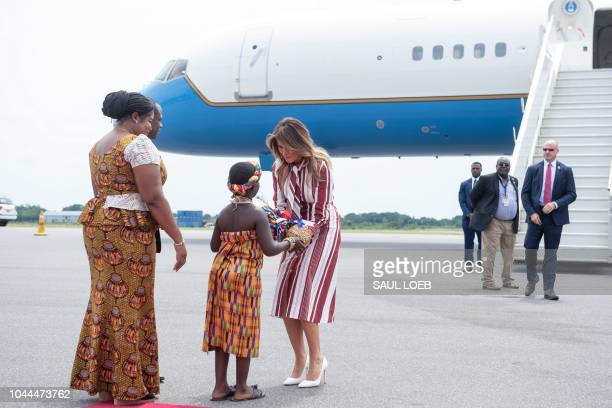US First Lady Melania Trump receives flowers during an arrival ceremony after landing at Kotoka International Airport in Accra October 2 2018 as she...