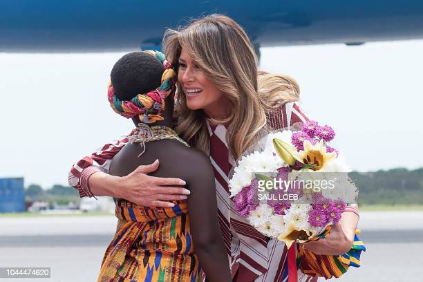 First Lady Melania Trump receives flowers during an arrival ceremony after landing at Kotoka International Airport in Accra October 2 2018 as she...