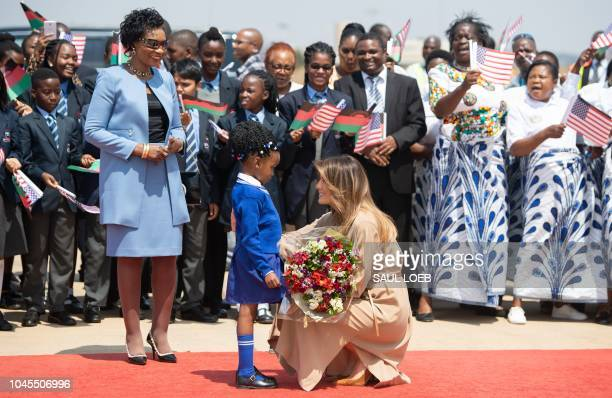 First Lady Melania Trump receives flowers from a young girl alongside the First Lady of Malawi Gertrude Mutharika as she arrives at Lilongwe...