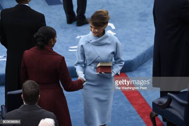 First lady Melania Trump shakes the hand of Former first lady Michelle Obama on January 20 2016 at the Capitol in Washington DC Trump is sworn in as...