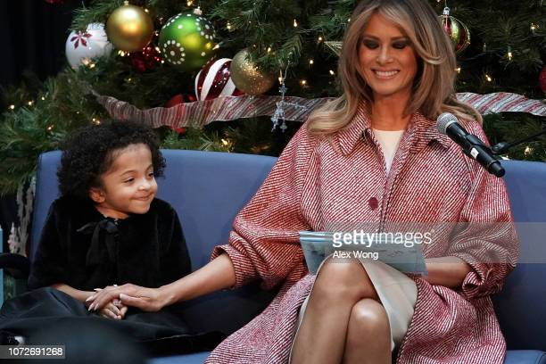 S first lady Melania Trump shares a moment with patient escort Tearrianna CookeStarkey while reading the story 'Oliver the Ornament' during a visit...